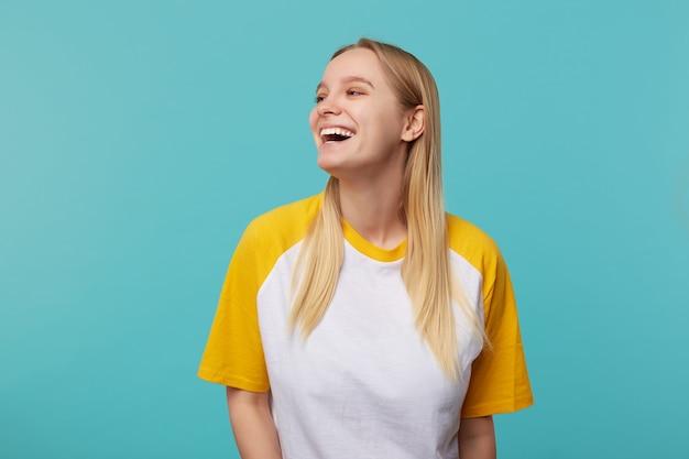 白と黄色のtシャツの青い背景の上に立っている間広い笑顔で喜んで脇を探しているカジュアルな髪型の陽気な若い魅力的な長い髪のブロンドの女性