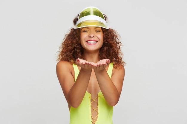 陽気な若い魅力的な赤い髪の巻き毛の女性、ネオンバイザーは彼女の手のひらを上げて、白い背景の上に立っている間カメラで幸せに笑っています