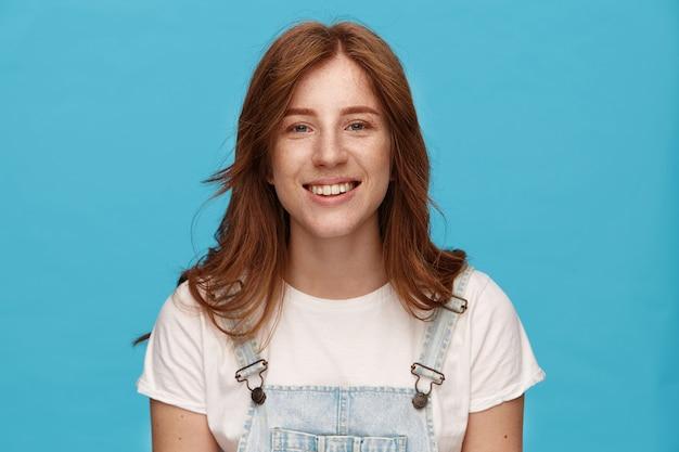 Allegro giovane femmina rossa attraente che mostra i suoi denti bianchi perfetti mentre sorride felicemente alla macchina fotografica, vestito in abiti casual mentre posa su sfondo blu