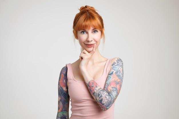 白い背景で隔離の魅力的な笑顔でカメラを見ながら彼女のあごに人差し指を保つお団子の髪型を持つ陽気な若い魅力的な赤毛の女性