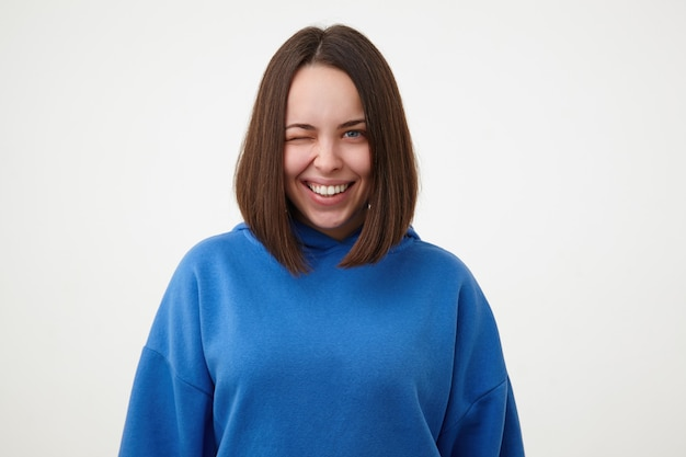 Cheerful young attractive short haired blue-eyed woman with bob haircut smiling gladly while winking at front, dressed in blue hoodie while posing over white wall