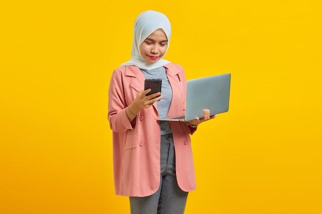 노란색 배경에 고립되어 서 있는 동안 노트북과 휴대폰을 사용하는 쾌활한 젊은 매력적인 여성