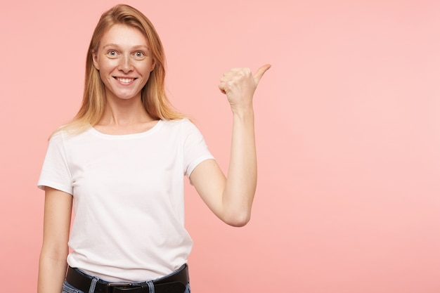 Cheerful young attractive woman with loose foxy hair showing happily aside with raised hand and smiling widely at camera, standing against pink background