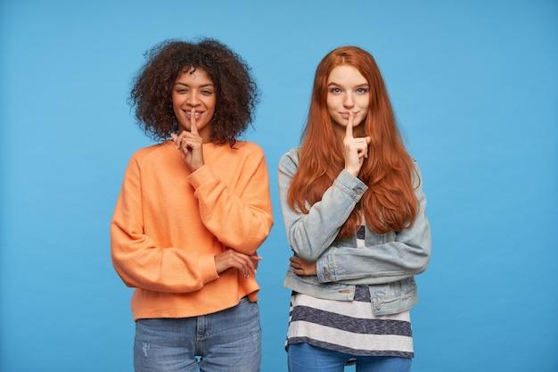 쾌활한 젊은 매력적인 여성이 입술에 검지 손가락을 들고 긍정적으로 웃고 파란색 벽 위에 서있는 동안 비밀을 유지하도록 요구합니다.
