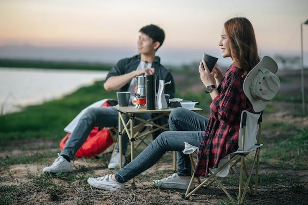 Веселая молодая пара пеших туристов сидит перед палаткой в лесу с кофейным сервизом и делает свежую кофемолку во время похода на летние каникулы, выборочный фокус