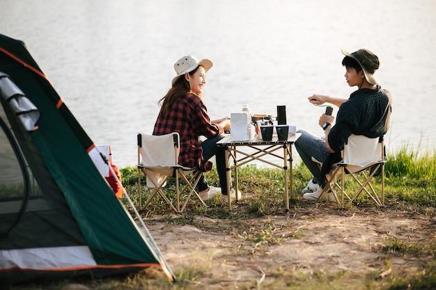 쾌활한 젊은 백패커 커플은 여름 방학 동안 캠핑을 하면서 커피 세트를 들고 숲 속의 텐트 앞에 앉아 신선한 커피 그라인더를 만들고 있다