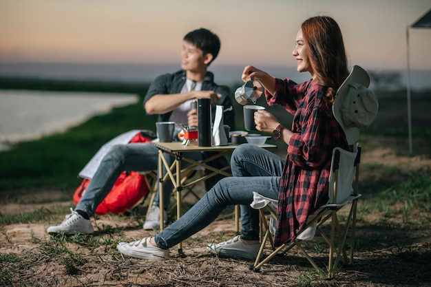 Cheerful young backpacker couple sitting at front of the tent in forest with coffee set and making fresh coffee grinder while camping trip on summer vacation, selective focus