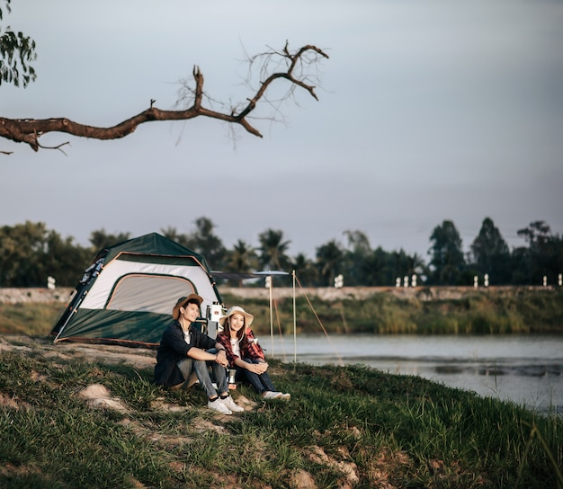 Cheerful young backpacker couple sitting at front of the tent near lake with coffee set and making fresh coffee grinder while camping trip on summer vacation