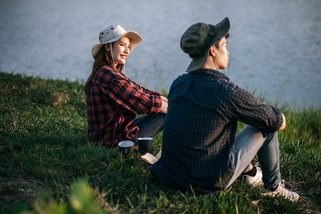 Cheerful young backpacker couple sitting on grass and looking forward over lake in early morning and making fresh coffee grinder while camping trip on summer vacation