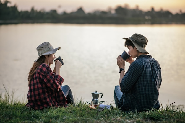 Cheerful young backpacker couple sitting on grass near lake in early morning and making fresh coffee grinder while camping trip on summer vacation