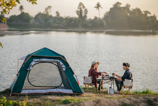 Cheerful young backpacker couple wearing trekking hat sitting near lake with coffee and breakfast and making fresh coffee grinder while camping trip on summer vacation