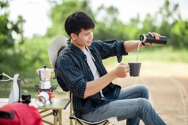 여름 방학 동안 캠핑을 하는 동안 커피 세트와 신선한 커피 분쇄기를 만드는 쾌활한 젊은 배낭 남자는 숲에 텐트 앞에 앉아