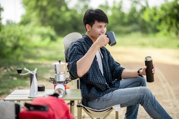 夏休みのキャンプ旅行中にコーヒーセットと淹れたてのコーヒーグラインダーを作る森のテントの前に座っている陽気な若いバックパッカーの男