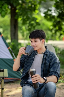 Cheerful young backpacker man sitting at front of the tent in forest with coffee set and making fresh coffee grinder while camping trip on summer vacation