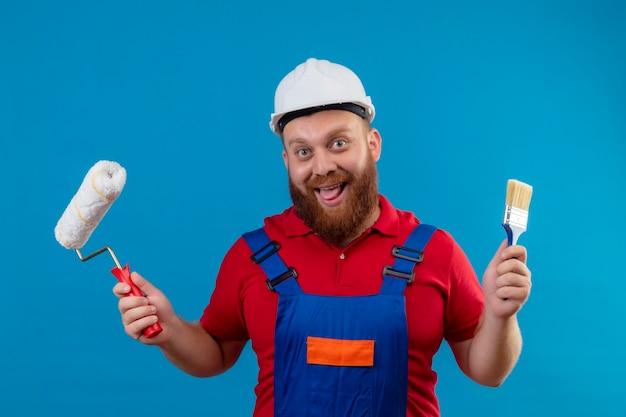 Allegro giovane barbuto uomo costruttore in uniforme da costruzione e casco di sicurezza che tiene il rullo di vernice e il pennello che attacca fuori la lingua felice e positivo