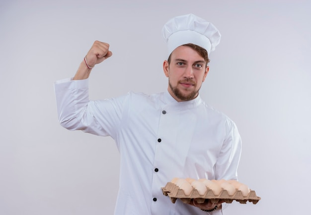A cheerful young bearded chef man wearing white cooker uniform and hat holding a carton of eggs with clenched fist while looking on a white wall