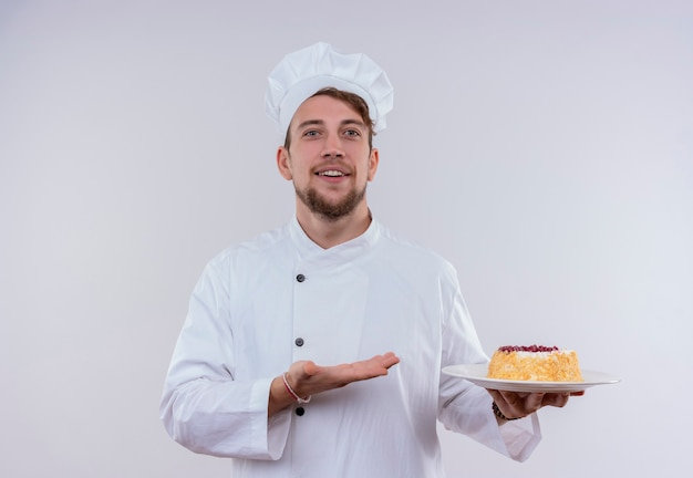 Un allegro giovane chef barbuto uomo che indossa l'uniforme bianca del fornello e il cappello che mostra un piatto con la torta mentre guarda su un muro bianco