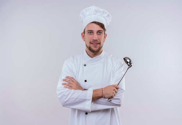 A cheerful young bearded chef man in white uniform holding ladle while looking on a white wall