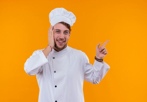 Un allegro giovane chef barbuto uomo in uniforme bianca rivolta verso l'alto con il dito indice mentre si tiene la mano sul viso e guardando su una parete arancione