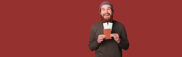Веселый молодой бородатый хипстер мужчина держит паспорт для путешествия и билеты на самолет