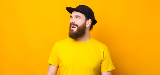 コピースペースを見て、笑顔の陽気な若いひげを生やしたヒップスターの男