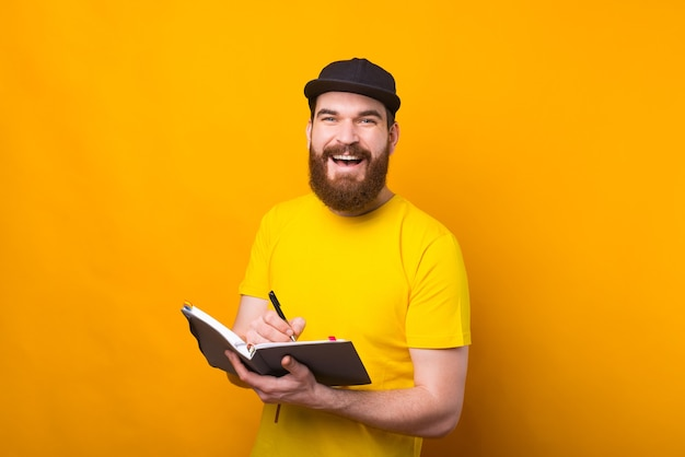 Cheerful young bearded hipster man writing in agenda and smiling