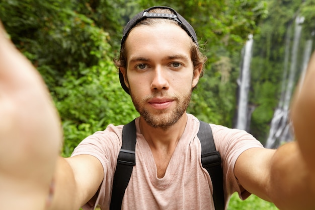 Cheerful young bearded hipster wearing baseball cap taking selfie in his exotic vacations