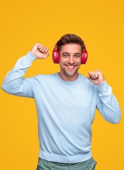 Веселый молодой бородатый мужчина в повседневной одежде веселится и танцует, слушая музыку через беспроводные наушники на желтом фоне