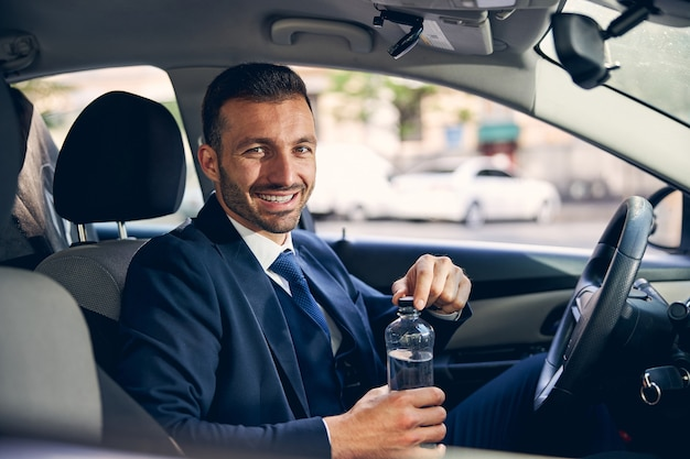 Веселый молодой бородатый мужчина сидит в своей машине и собирается пить воду, прежде чем покинуть свой автомобиль