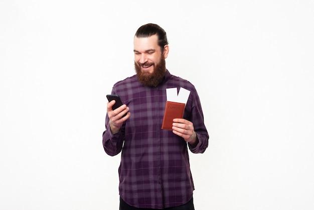 Веселый молодой бородатый мужчина покупает билеты онлайн с помощью смартфона