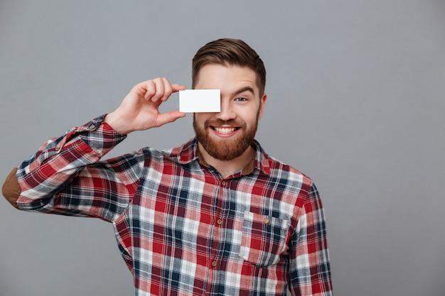 Giovane uomo barbuto allegro che tiene biglietto da visita in bianco