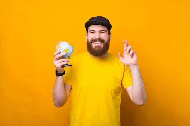 Cheerful young bearded man holding globe and crossing fingers over yellow background