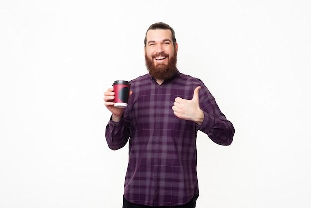 カジュアルな陽気な若いひげを生やした男は、親指を立てて、行くためにコーヒーのカップを保持しています