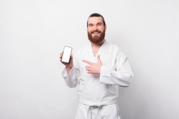 Веселый молодой бородатый мужчина в униформе тхэквондо, указывая на пустой экран смартфона