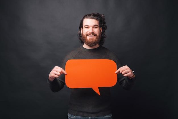 Веселый молодой бородатый мужчина держит речи пузырь глядя