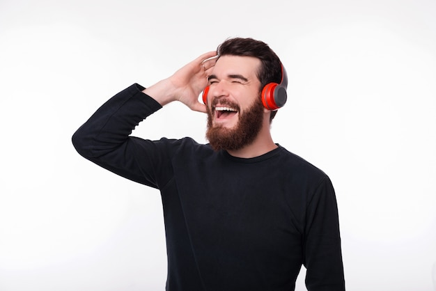 Cheerful young bearded man is listening to music in his earphones, singing on white space.