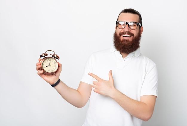 元気な若いひげを生やした男が目覚まし時計を指しています。