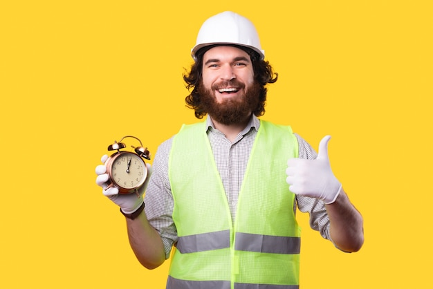 A cheerful young bearded man is showing a thumb up while looking at the camera and holding a little clock near a yellow wall