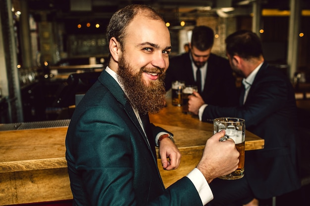 Cheerful young bearded man look on camera and smile. he hold mug of beer. two other people stand behind and talk.