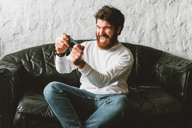 Cheerful young bearded man playing games at smartphone while sitting on sofa