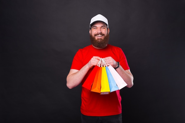 Cheerful young bearded man in red t-shirt holding colorful shopping bags over black background