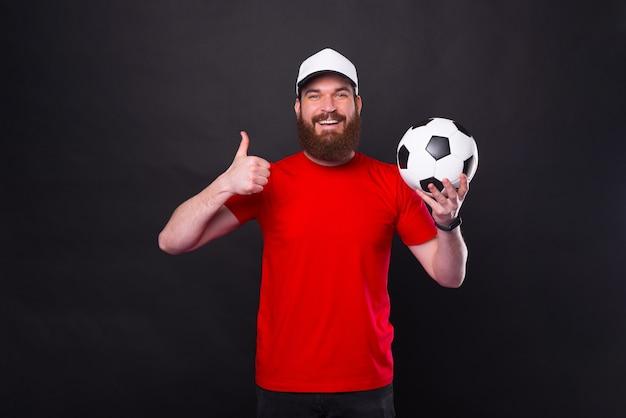 Веселый молодой бородатый мужчина показывает большой палец вверх жест и держит футбольный мяч