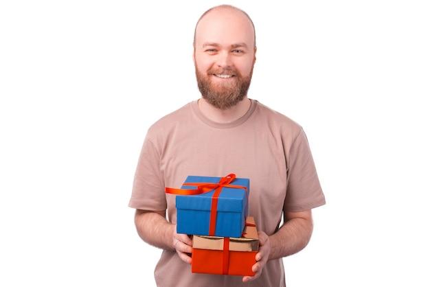 쾌활 한 젊은 수염 남자 웃 고 흰색에 두 개의 선물 상자를 들고