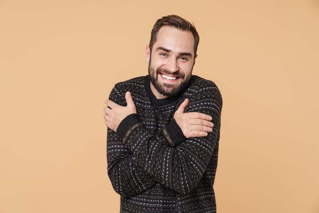 Веселый молодой бородатый мужчина в теплом свитере стоит изолированно над бежевой стеной и обнимает себя