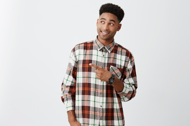 Cheerful young beautiful black man with afro hairstyle in stylish casual shirt smiling with teeth, pointing on free space, looking aside with excited and delight expression