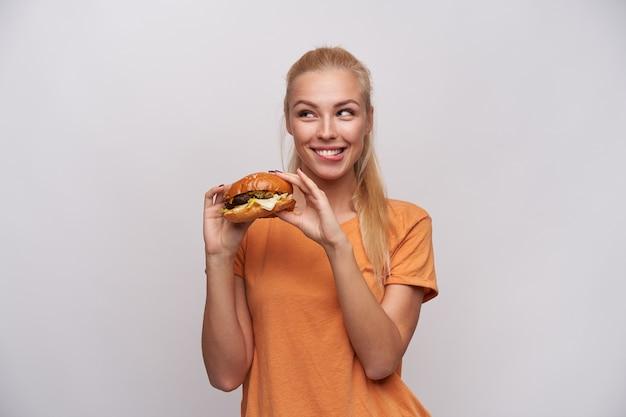 Allegro giovane bella donna bionda con acconciatura casual tenendo cheeseburger in mani alzate e guardando astutamente da parte con un ampio sorriso, isolato su sfondo bianco