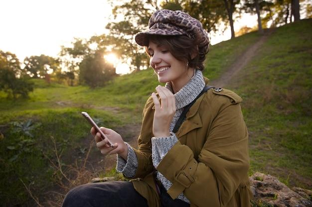陽気な若い美しい茶色の髪の女性、ボブの髪型で携帯電話を手に持って、友人からのメッセージを読んで、日没のぼやけた公園でポーズをとる
