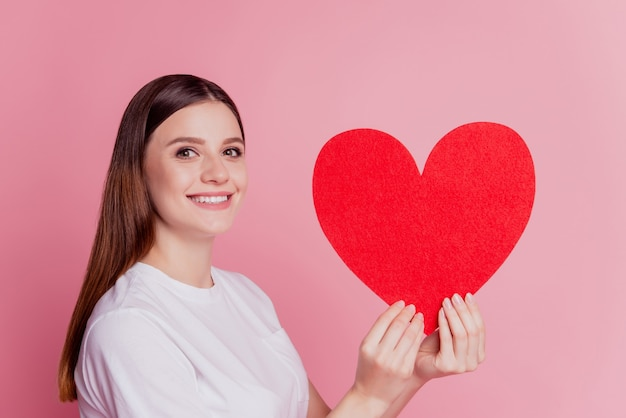 Cheerful young beautiful girl hold red paper heart with fingers