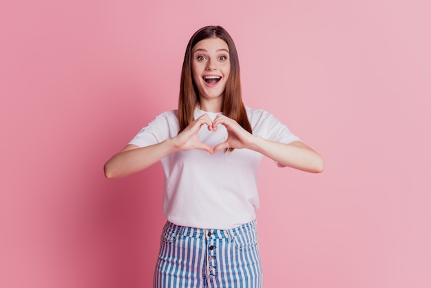 Cheerful young beautiful girl is gesturing a heart with fingers excited face look camera on pink wall