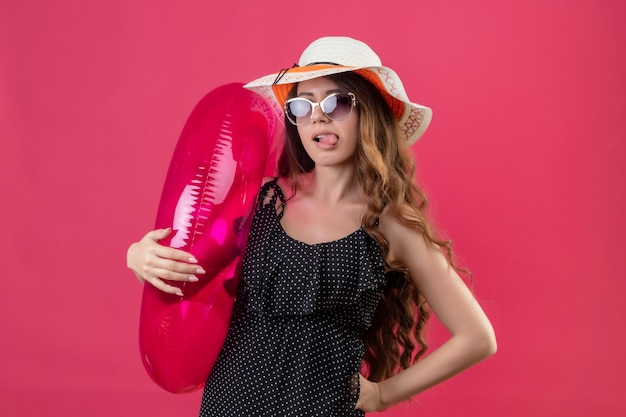 Cheerful young beautiful traveler girl in dress in polka dot in summer hat wearing sunglasses holding inflatable ring happy and positive sticking out tongue standing over pink space